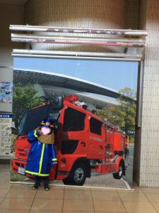消防車のスクリーンの前でコスチュームを着てパチリ